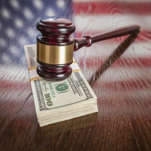 Wooden Gavel Resting on Stack of Money with American Flag Reflection on Table.